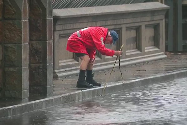What a legend! Elderly man takes it upon himself to help motorists stranded by Sydney flooding