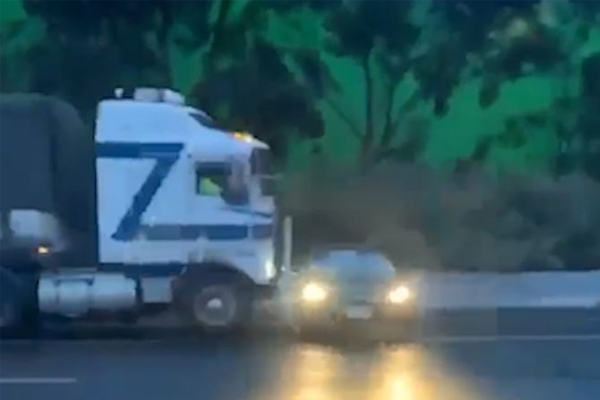 WATCH | Truck pushes car along wet freeway